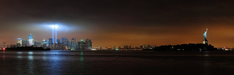 New York City Manhattan downtown skyline at night with statue of