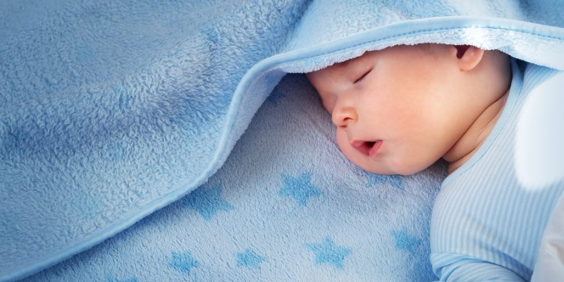 Three month old baby sleeping on blue blanket with stars