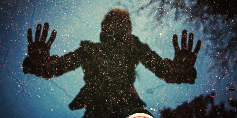 Reflection of person in puddle.
